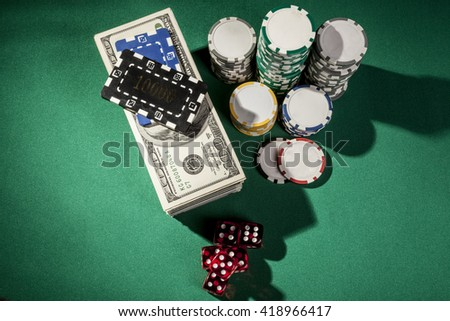 Money, dice and chips on green table - stock photo
