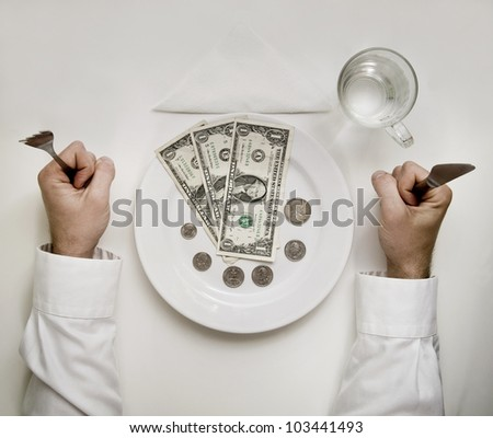 Money diet concept. Man holds fork and knife. Dollar bills and coins on plate isolated on white. - stock photo