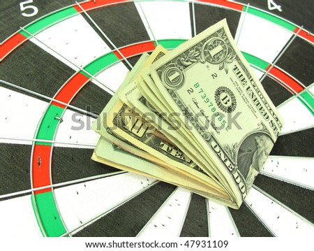 Money dollars on colorful darts target - stock photo