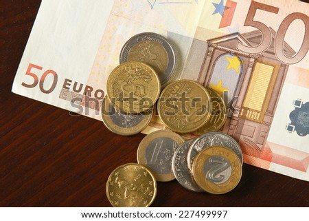 Money: euro coins and bills close up isolated on wood background - stock photo