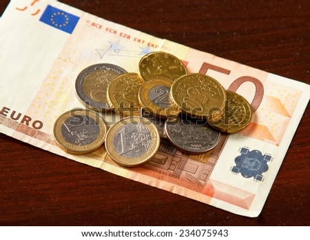 Money: euro coins and bills close up isolated on wood background. - stock photo