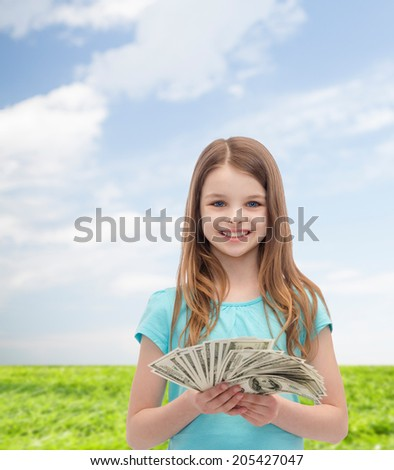 money, finances and people concept - smiling little girl with dollar cash money - stock photo
