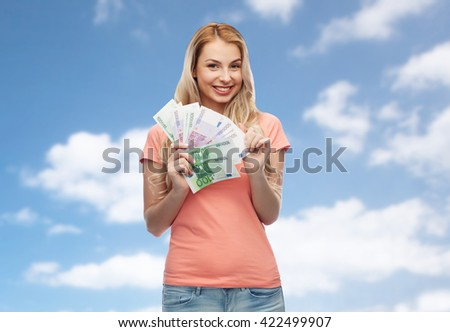 money, finances, investment, saving and people concept - happy young woman with euro cash money over blue sky and clouds background - stock photo