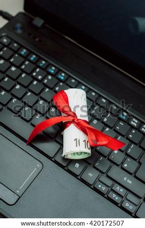 Money gift on a laptop keyboard. Get money online. - stock photo