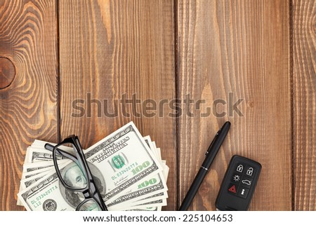 Money, glasses and car key on wooden table. View from above with copy space - stock photo