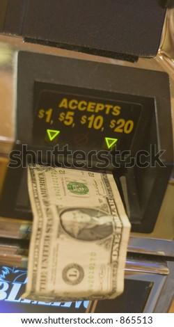 money going into slot machine - stock photo