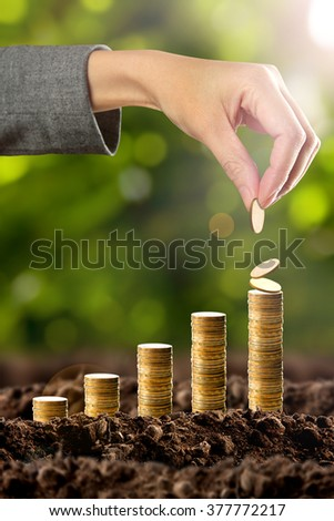 Money growing in soil with hand - stock photo