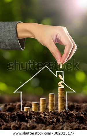 Money growing in soil with house - stock photo