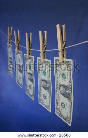 Money hanging on line. 5 US dollar bills. focus is on first dollar bill. - stock photo
