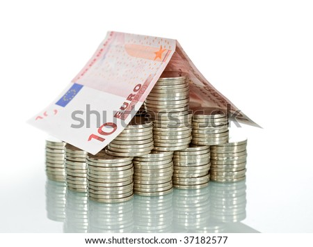 Money house made from lots of coins and a euro banknote roof - isolated with reflection - stock photo
