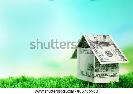Money house on green grass, close up - stock photo