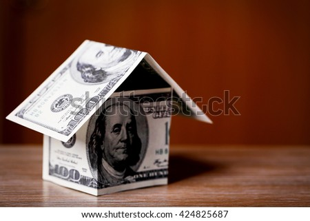 Money house on wooden table, close up - stock photo