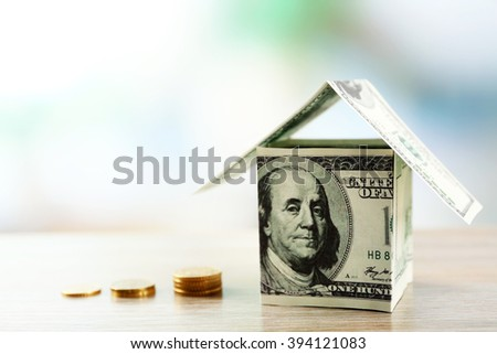 Money houses with stacks of coins on wooden table, close up - stock photo