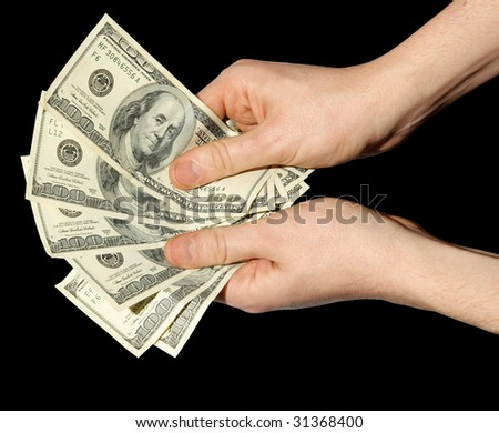 Money in a hand on a black background - stock photo