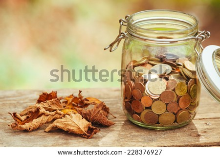 Money in a jar on a table next to some fallen leaves. - stock photo
