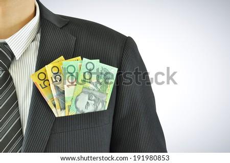 Money in businessman pocket suit - AUD - Australian Dollars - stock photo