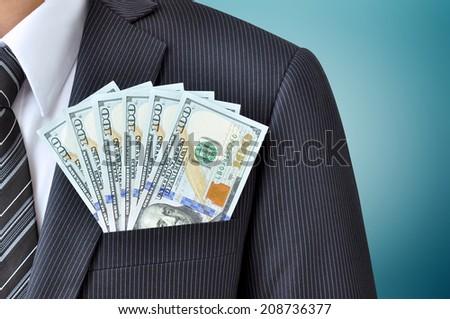 Money in businessman suit pocket  - United States dollars (USD) - stock photo