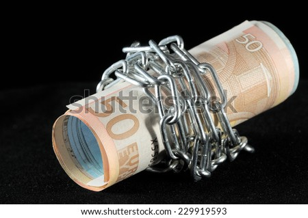 Money in chains that represents the crisis on a black background - stock photo