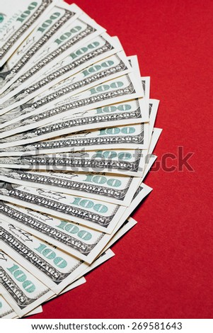 Money in dollars closeup, one hundred dollars banknotes, lying on red background - stock photo