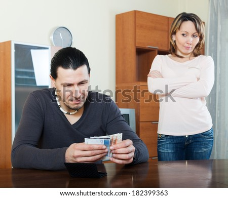Money in family. Man counting cash, woman watching him - stock photo