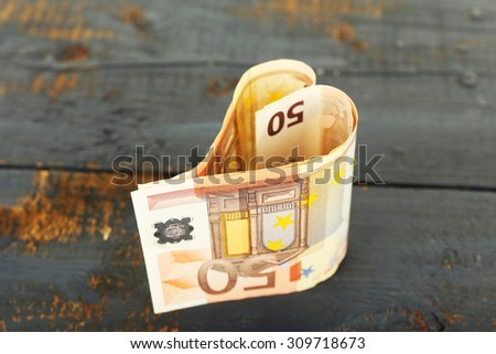 Money in form of heart on rustic wooden background - stock photo