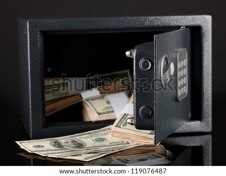 Money in open safe isolated on black - stock photo