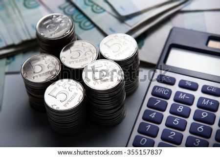 money in the form of banknotes and coins with calculator close up - stock photo