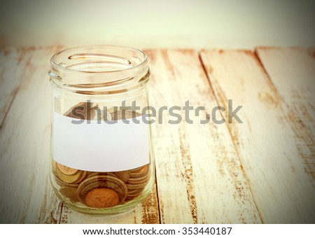 Money in the glass on wooden table with filter effect retro vintage style - stock photo