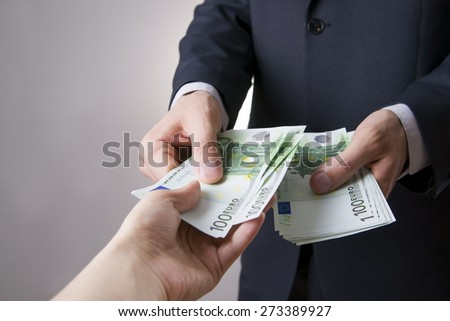Money in the hands of the people. To count euro on gray background - stock photo