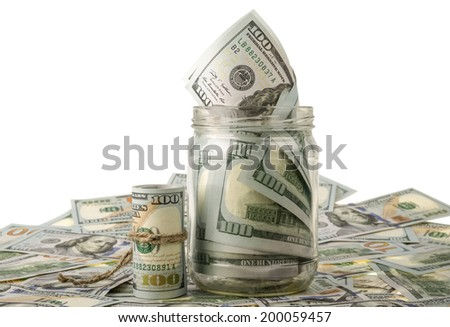 Money in the jar placing on US dollar banknotes  - stock photo