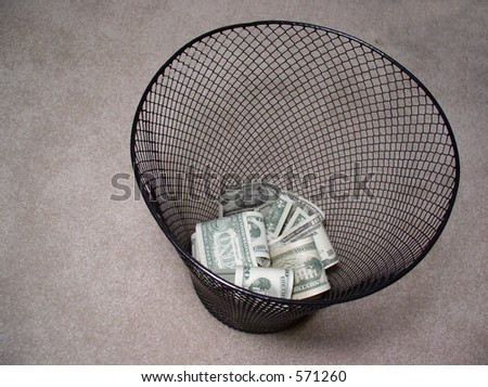 Money in trash basket - stock photo