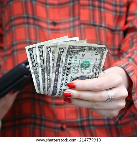 Money in woman's hand, A woman holding U.S. currency bills. - stock photo