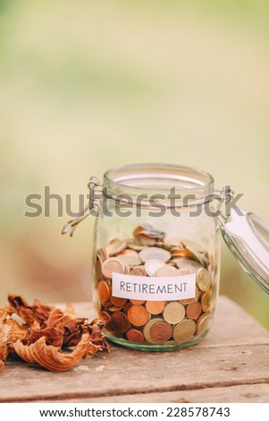 Money jar full of coins as a retirement fund. - stock photo