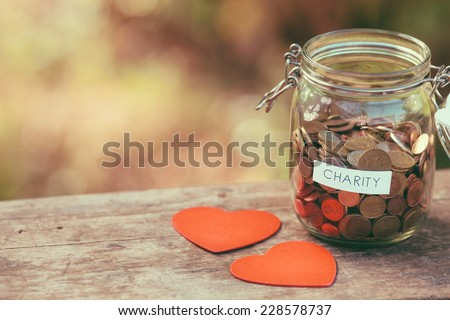 Money jar full of coins for charity and a couple of heart shapes - stock photo