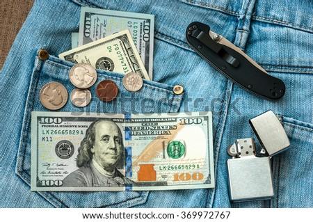 Money, knife, lighter. on jeans background. - stock photo