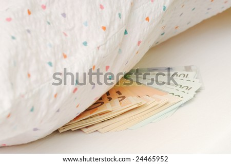 Money laid on bed under pillow - stock photo