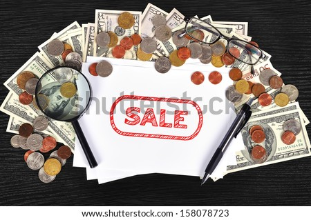 money on table and paper with sale symbol - stock photo
