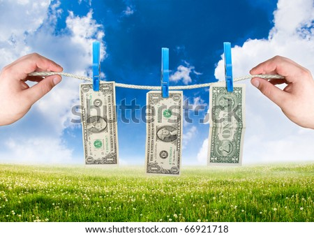 Money on the rope with hand. money laundering theme - stock photo