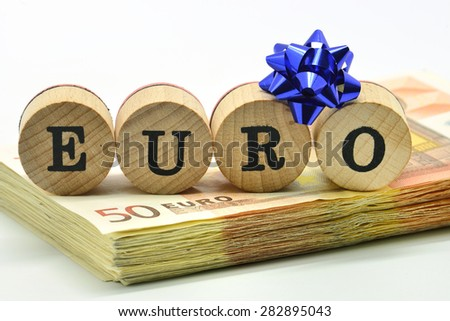 Money pile of 50 Euro banknotes isolated in white with euro wood letters and gift symbol - stock photo
