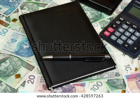 Money polish calendar notes and pen on the wooden table - stock photo