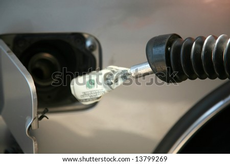 money pouring out of a gas nozzle while filling up a car or truck - stock photo