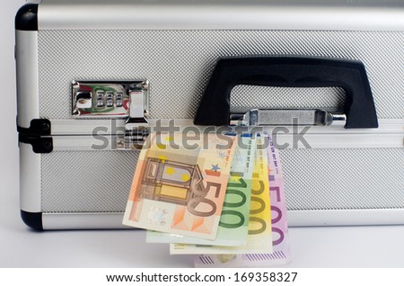Money protrudes from metal suitcase with numerical code - stock photo