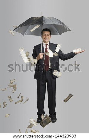 Money raining over a businessman - stock photo