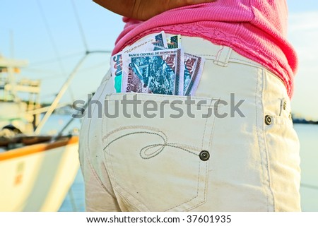 Money sticking out of back pocket of girl - stock photo
