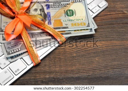 Money Tied With A Ribbon On The Computer Keyboard On The Rough Wood Background - stock photo