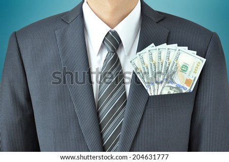 Money - United States dollar (USD) bills - in businessman suit pocket - stock photo