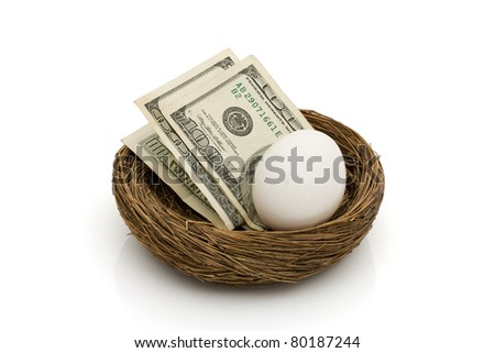 Money with an egg in a nest isolated on white, Saving for your retirement - stock photo