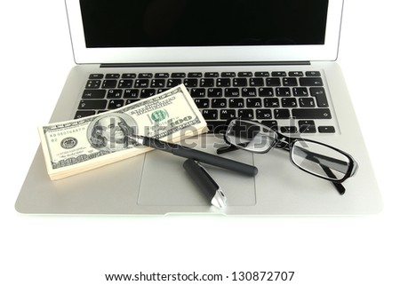 Money with glasses and pen on laptop isolated on white - stock photo