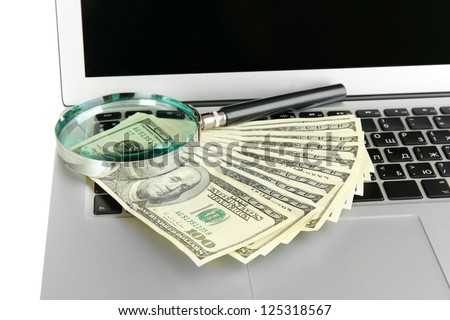 Money with magnifying glass on laptop close-up - stock photo