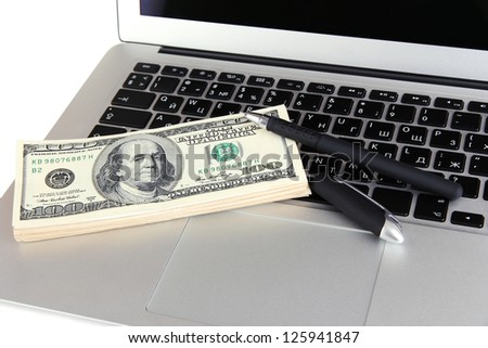 Money with pen on laptop close-up - stock photo